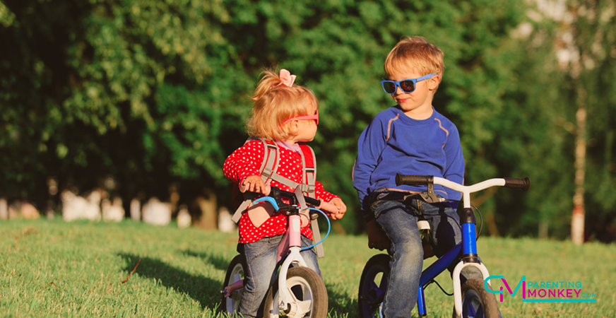 Two kids riding balance bikes in a park.