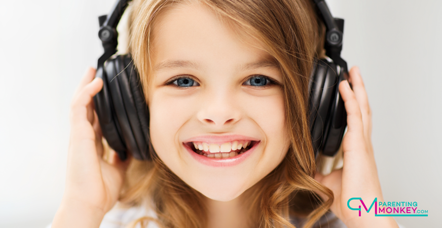 Girl, smiling listening to music with large headphones.