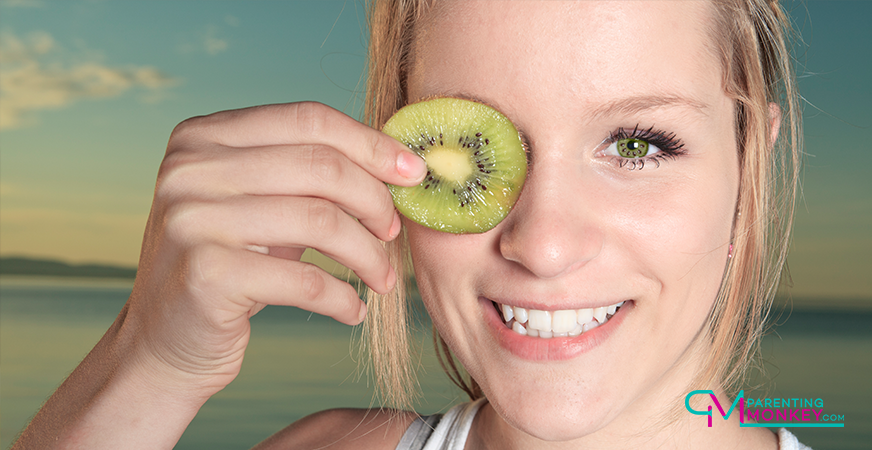 Teenage girl holding a slice of kiwi fruit to her eye.