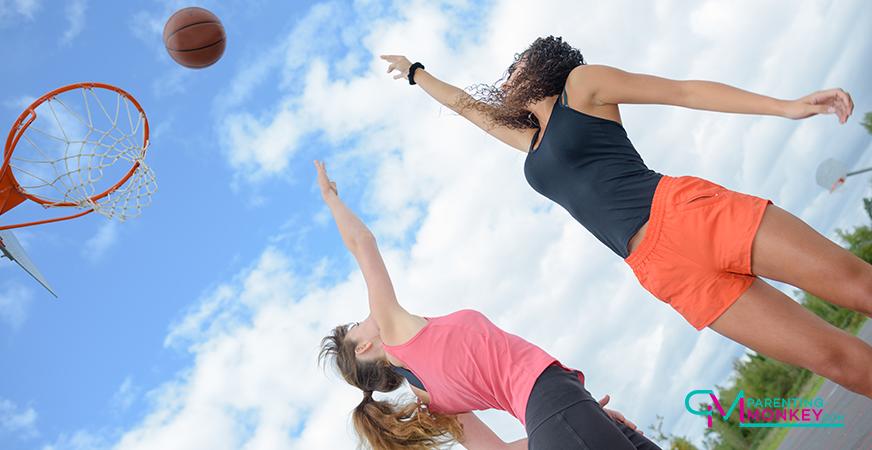 To girls playing basketball.
