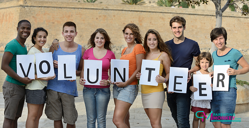 9 teenage students holding signs that spell the word volunteer.